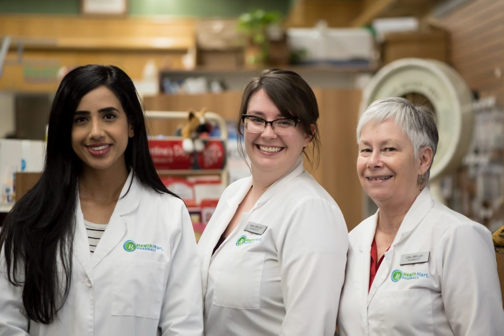 an image of 3 female pharmacists standing together in their white lab coats smiling for a photograph inside the Corner Drug Store