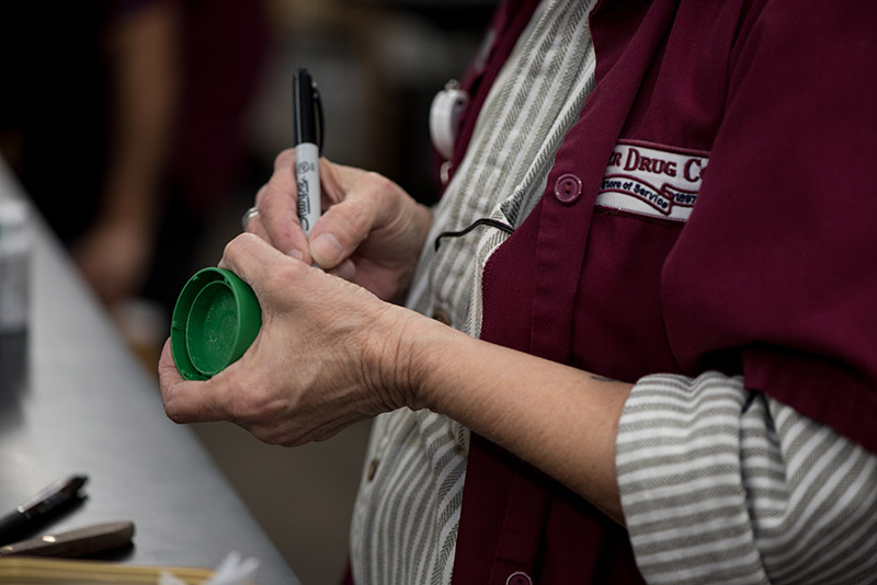 an image of a Corner Drug Co. employee in a red smock writing on a medicine bottle with a Sharpie pen.